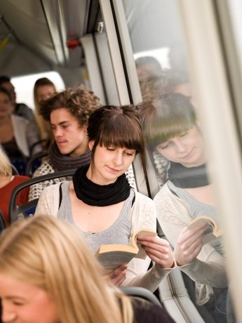 Young woman reading a book while going by the bus
